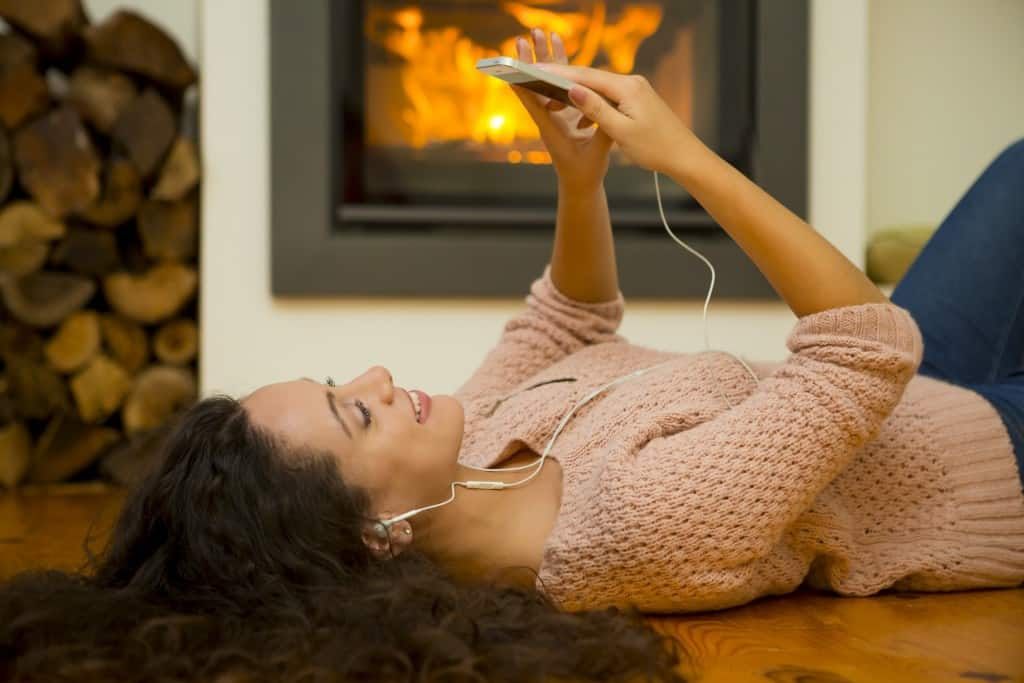 Beautiful woman listen music at home at the warmth of a fireplace